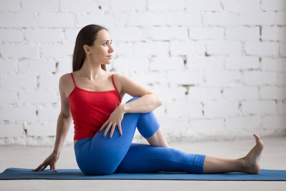 Young woman in exercise clothes performing the seated spinal stretch