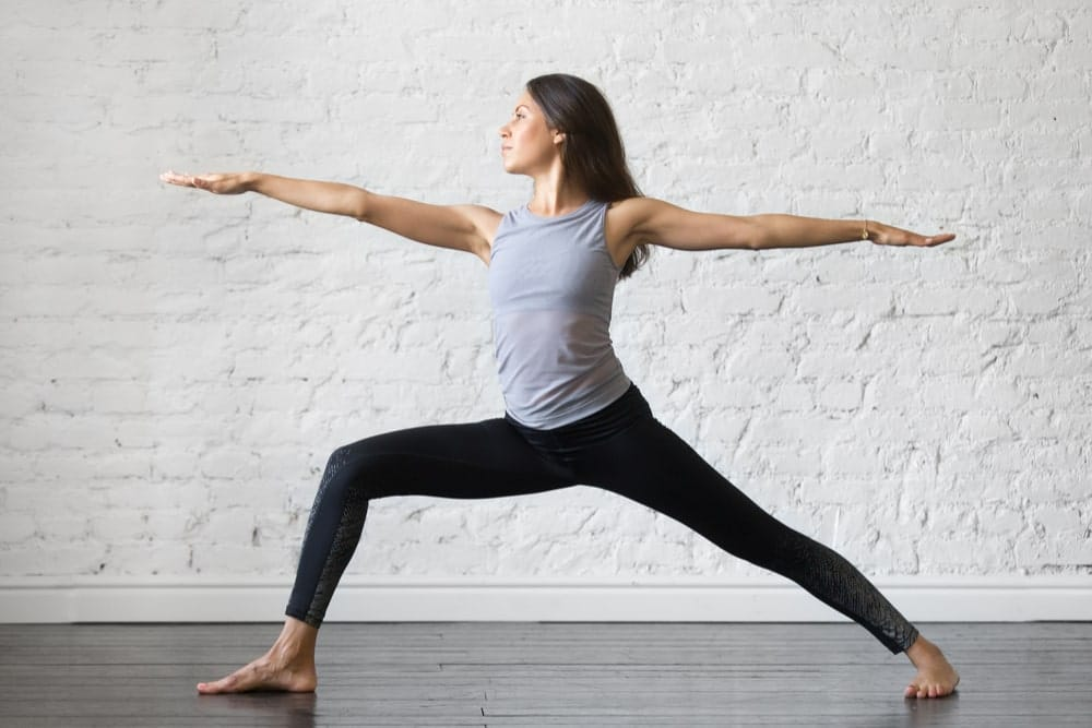 Young woman in exercise clothes performing the warrior pose