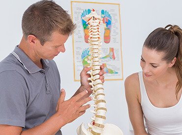 chiropractor explaining spinal anatomy before back adjustment