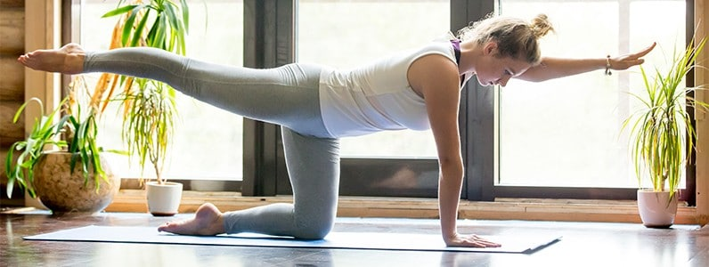 woman doing yoga to strengthen her spine