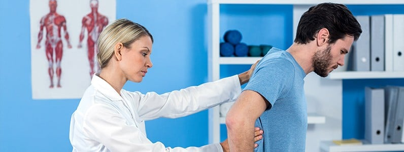 chiropractor examining a patient's thoracic spine